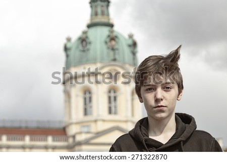 portrait of a teenage boy in front of the Schloss Charlottenburg, Berlin - stock photo