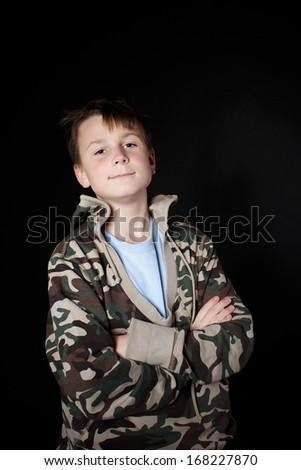 Portrait of a teenage boy on a black background - stock photo