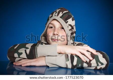 Portrait of a teenage boy on a blue background - stock photo