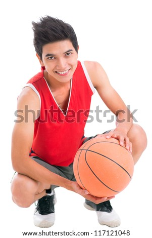 Portrait of a teenage boy with basketball looking at camera and smiling - stock photo
