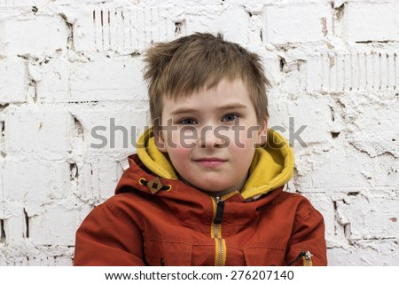 portrait of a teenage boy with rough hair looking with a grin straight into the camera at a white brick wall background - stock photo