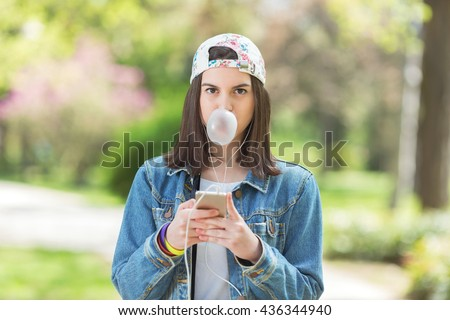 Portrait of a teenage girl blowing a bubble of chewing gum while using phone and listening to music on her headphones. She is wearing denim jacket and a baseball cap.