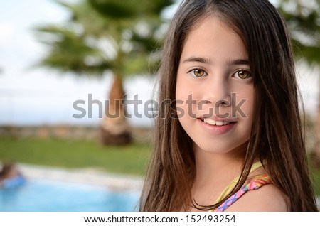 Portrait of a teenage girl by the pool - 11 year old girl enjoying the summer vacation by the pool on the Greek island of Crete - stock photo