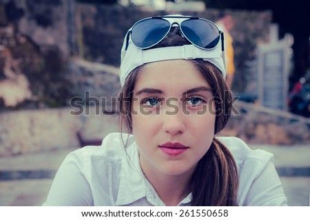 Portrait of a teenage girl in a baseball cap and sunglasses on a head - stock photo