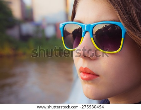 Portrait of a teenage girl in colorful sunglasses close up - stock photo