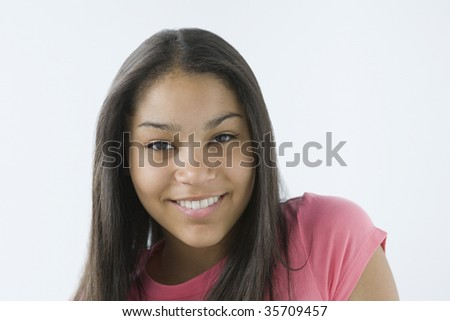 Portrait of a teenage girl smiling into camera.
