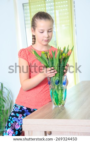 portrait of a teenage girl with flowers at home - stock photo