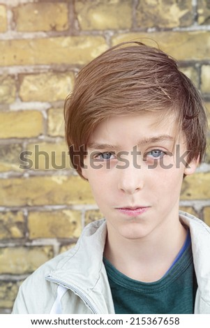 portrait of a teenager boy in front of a brick wall - stock photo
