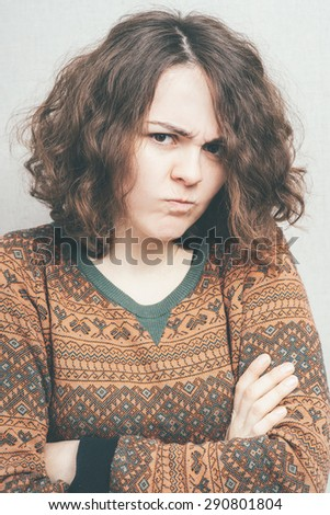 Portrait of a teenager brunette girl with pouting sad expression - stock photo