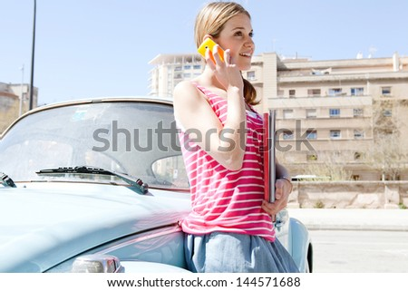 Portrait of a teenager girl having a phone call conversation with her smartphone while sitting on a classic colorful car in a city during a sunny day with a blue sky, smiling. - stock photo