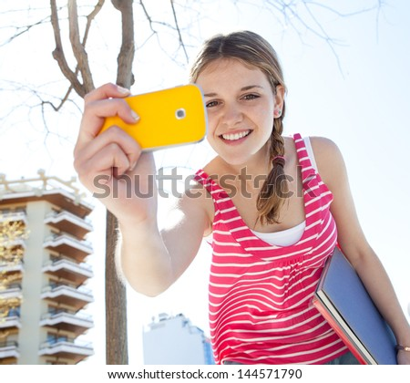 Portrait of a teenager girl using with her colorful smartphone to take photos in the city during a sunny day with a blue sky, smiling. - stock photo