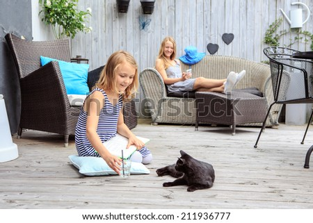 portrait of a teenager girl with a cat in the backyard