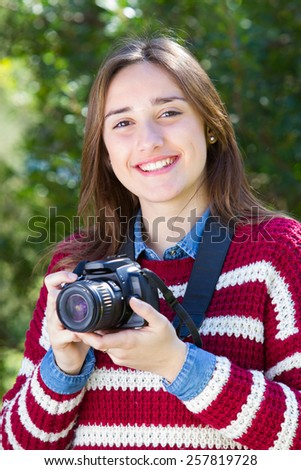 Portrait of a teenager holding photo camera - stock photo