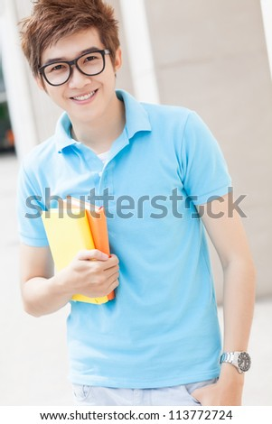 Portrait of a teenager in glasses holding books - stock photo