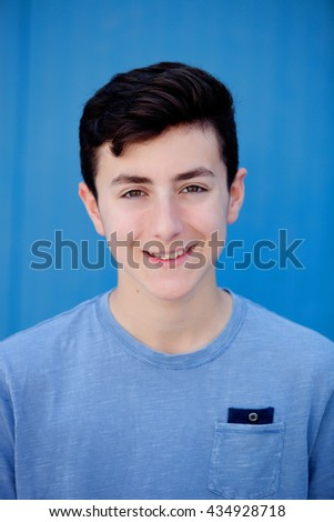 Portrait of a teenager rebellious man with a blue background - stock photo