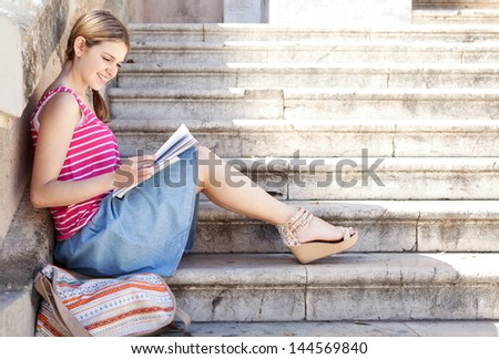 Portrait of a teenager student girl reading from her notebook while sitting down on a university campus entrance stone steps, smiling during  a sunny day.