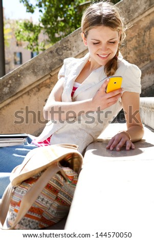 Portrait of a teenager student using her smart phone while sitting down at a college stone steps during a sunny day, smiling. - stock photo