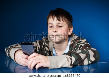 portrait of a teenager with a phone on a blue background - stock photo