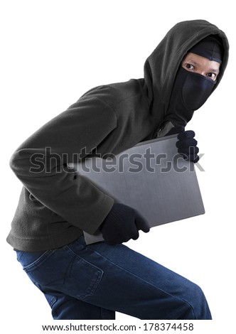 Portrait of a thief stealing a laptop computer - stock photo