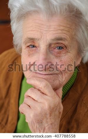 Portrait of a thinking elderly woman - stock photo