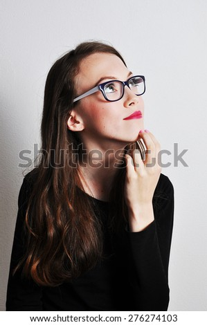 Portrait of a thinking girl on a light grey background