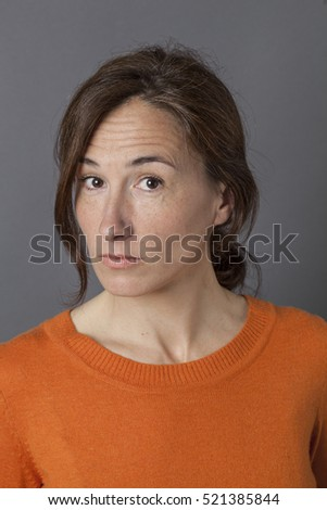 portrait of a thinking middle aged woman expressing surprise and doubt with a touch of pride, grey background studio