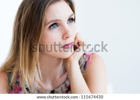 Portrait of a thinking woman looking up - stock photo