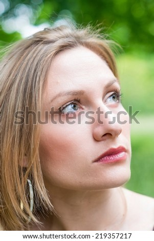 Portrait of a thinking woman looking up on the nature