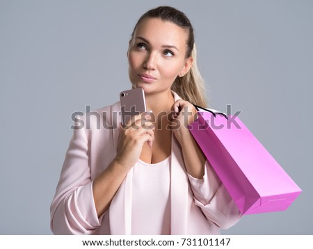 Portrait of a thinking woman with pink shopping bag and mobile phone. Attractive cheerful female holds the  bag with purchasing.