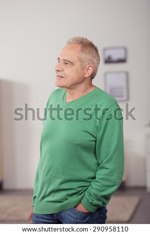 Portrait of a Thoughtful a Middle Aged Man in Casual Clothing, Standing Inside the House While Looking Into Distance with Hand on his Pocket - stock photo
