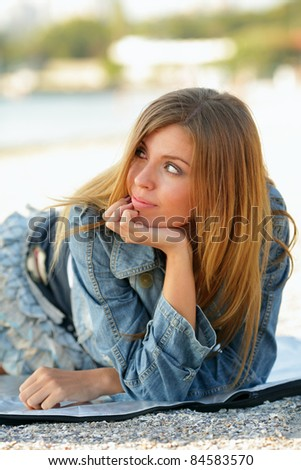 Portrait of a thoughtful beautiful young woman at the beach