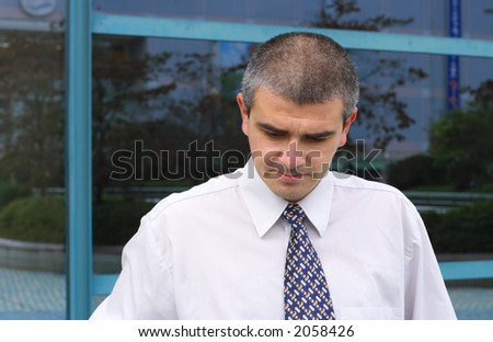 Portrait of a thoughtful businessman in front of blue corporate building windows