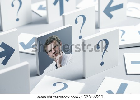 Portrait of a thoughtful businessman surrounded by question marks and arrows - stock photo