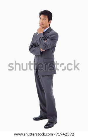 Portrait of a thoughtful businessman with the arms crossed against a white background