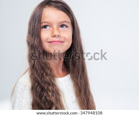 Portrait of a thoughtful little girl looking up isolated on a white background - stock photo