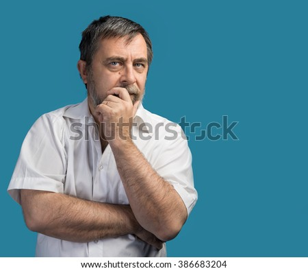 Portrait of a thoughtful middle-aged man posing on a blue background with copyspave