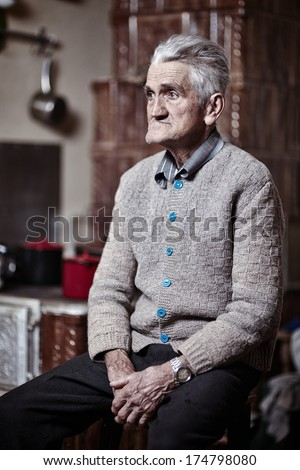 Portrait of a thoughtful old man indoor with selective focus - stock photo