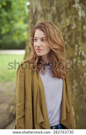 Portrait of a Thoughtful Pretty Blond Teen Girl In Front a Big Tree Trunk, Looking Into the Distance. - stock photo