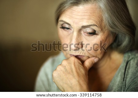 Portrait of a thoughtful sad elderly woman - stock photo