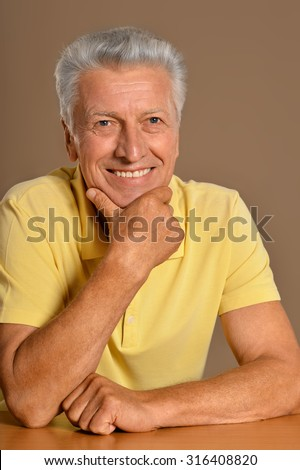 Portrait of a thoughtful smiling elder man on  background