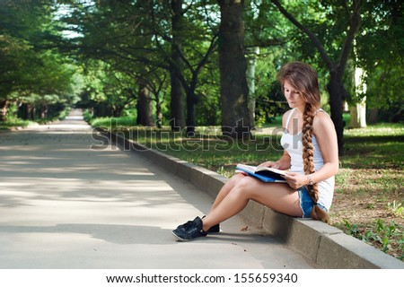 Portrait of a thoughtful teenage girl reading book in the park - stock photo