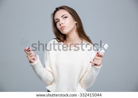 Portrait of a thoughtful woman holding saving light bulb and normal light bulb over gray background - stock photo
