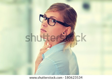 Portrait of a thoughtful young woman in blue shirt and glasses (student, secretary or businesswoman) - stock photo