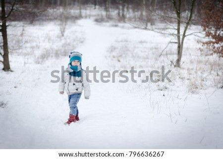 Portrait of a three year old boy, who is walking on a winter forest, and have fun of that