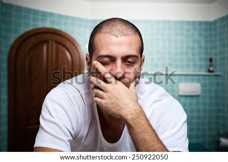 Portrait of a tired man looking in the mirror in his bathroom