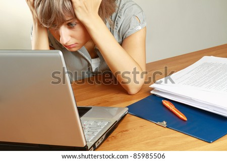 Portrait of a tired young businesswoman in front of a laptop, blueprint - stock photo