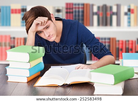 Portrait Of A Tired Young Man Studying In Library