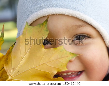 Portrait of a toddler child, boy or girl, with yellow autumn or fall maple leaf.