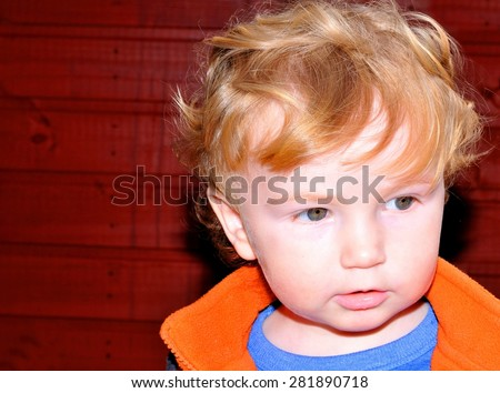 Portrait of a toddler on dark red background  - stock photo
