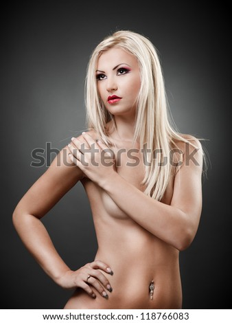 Portrait of a topless blond woman holding hand on shoulder
